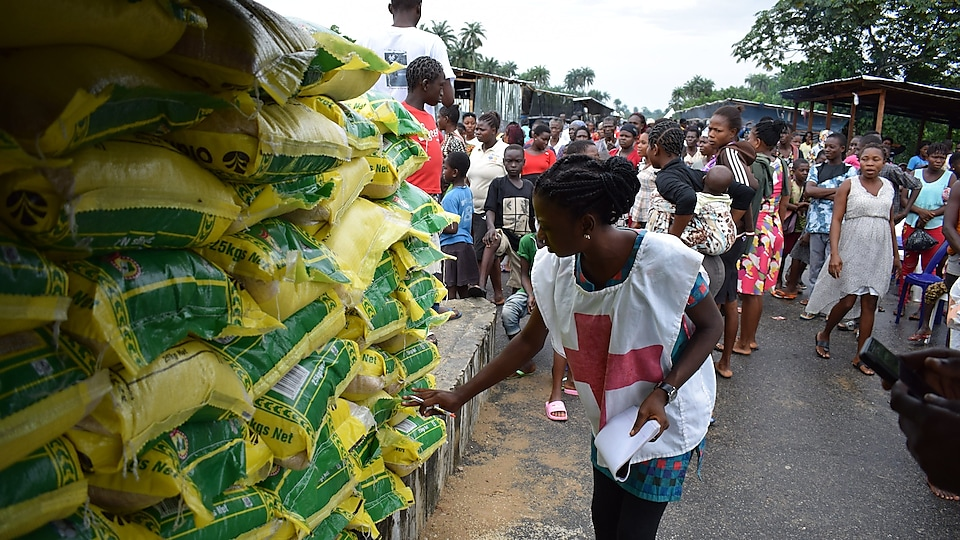A Red-Cross officer takes record of SPDC JV relief materials for flood victims at Patani IDP Camp in Delta State.