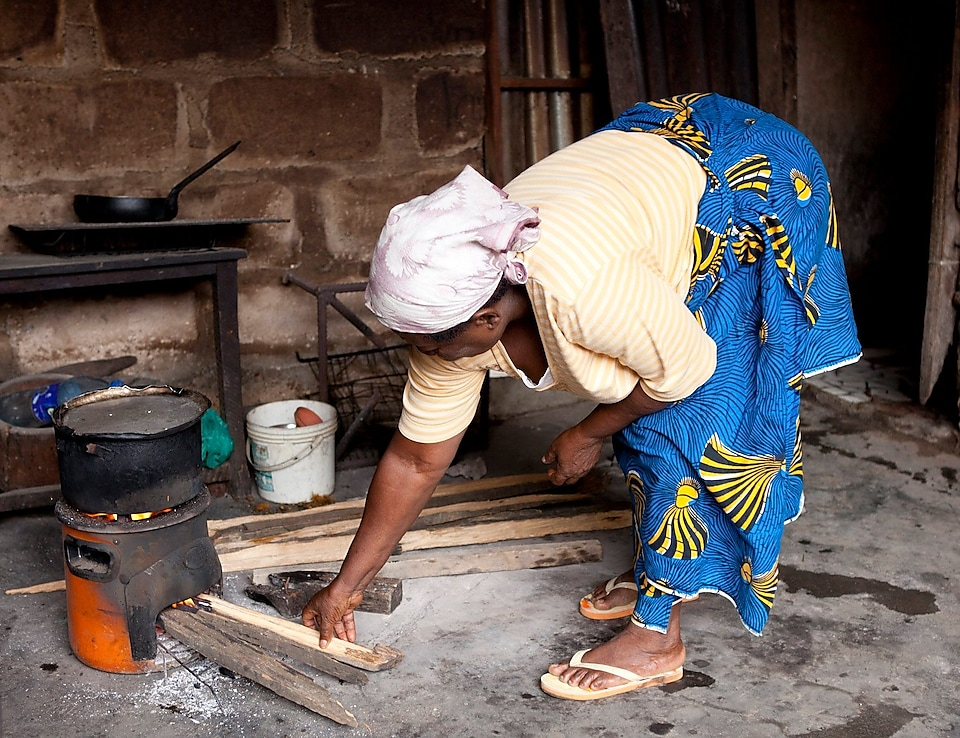 Lady cooking on a cookstove in Nigeria